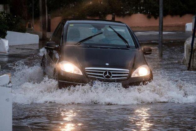 Un coche transita una calle inundada de Cala de Bou (Ibiza) en una jornada en la que la borrasca Gloria,...