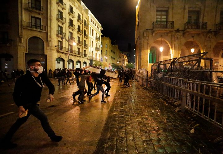 Anti-government protesters throw stones against the riot police, during ongoing protests against the political elites who hav