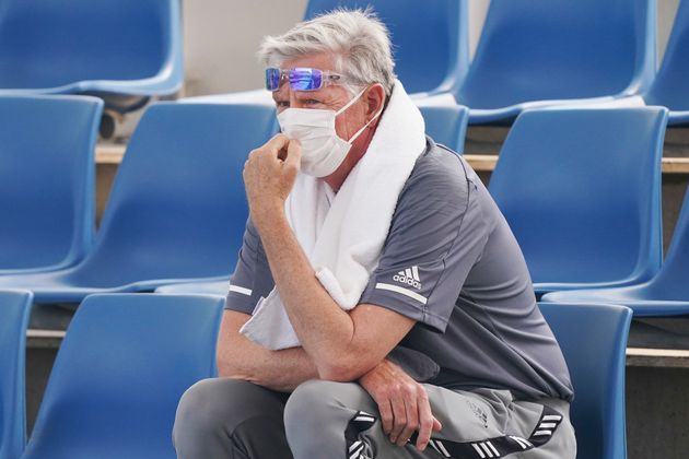 A spectator wears a mask as smoke haze shrouds Melbourne during an Australian Open practice session at...