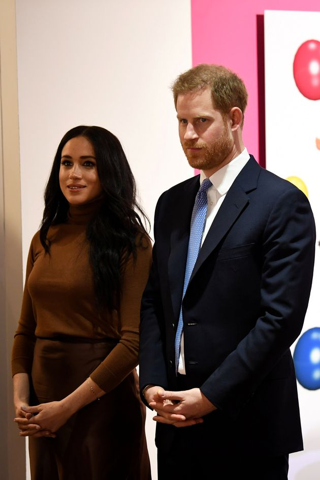 Britain's Prince Harry and his wife Meghan, Duchess of Sussex react as they view a special exhibition...
