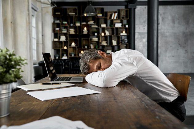 Portrait of mature business man sleeping on desk in