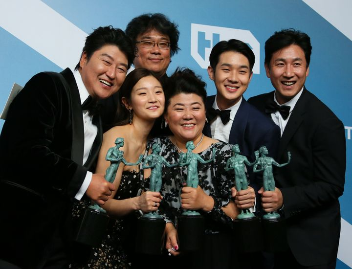 """""""Parasite"""" cast (L-R) Song Kang-ho, Cho Yeo-jeong, director Bong Joon-ho, Lee Jung-eun, Choi Woo-shik, and Lee Sun-kyun pose with the trophy for Outstanding Performance by a Cast in a Motion Picture in the press room during the 26th Annual Screen Actors Guild Awards at the Shrine Auditorium in Los Angeles on January 19, 2020."""