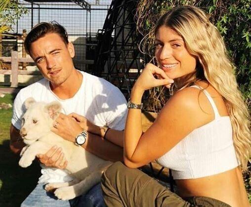 Elsa Dasc et Arthur Vencet posant avec un lionceau dans un zoo privé de