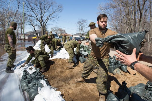 Members of the Canadian Armed Forces help move sandbags near Ottawa on April 28, 2019, as rising waters...