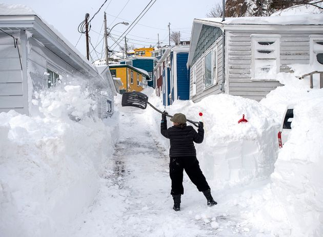 A woman clears snow off a roadway in St. John's on Sunday, days after a major winter storm wreaked havoc...
