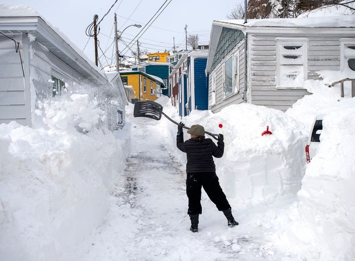 A woman clears snow off a roadway in St. John's on Sunday, days after a major winter storm wreaked havoc on parts of Newfoundland with massive amounts of snowfall.