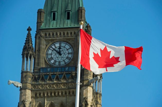 A Canadian flag flies near the Peace Tower on Parliament Hill in Ottawa on Oct. 23,