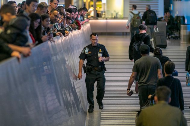 An airport officer walks past international travelers arriving to Los Angeles International Airport for...