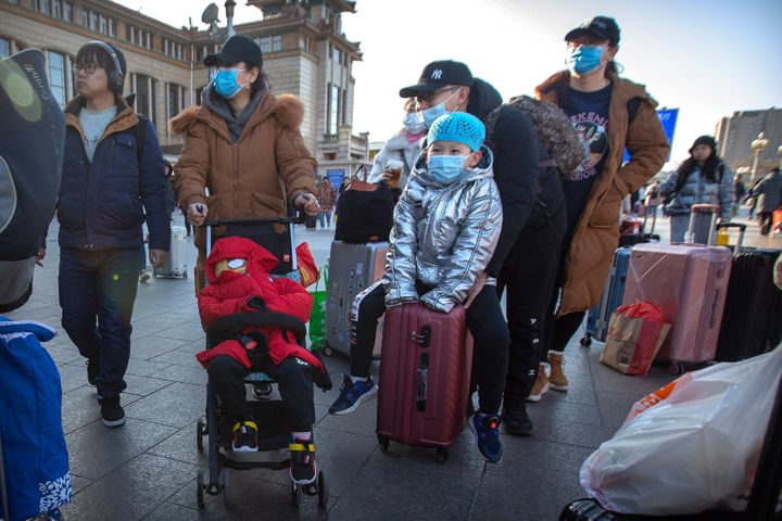 Travelers wear face masks outside of the Beijing Railway Station on Jan. 20, 2020. China reported a sharp rise in the number