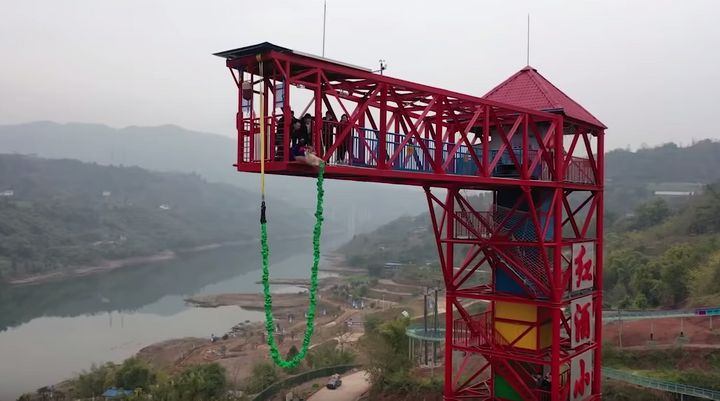 A still of the pig being taken to the edge of the bungee jumping tower.