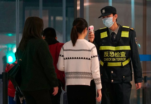 An airport staff member uses a temperature gun to check people leaving Wuhan Tianhe International Airport...