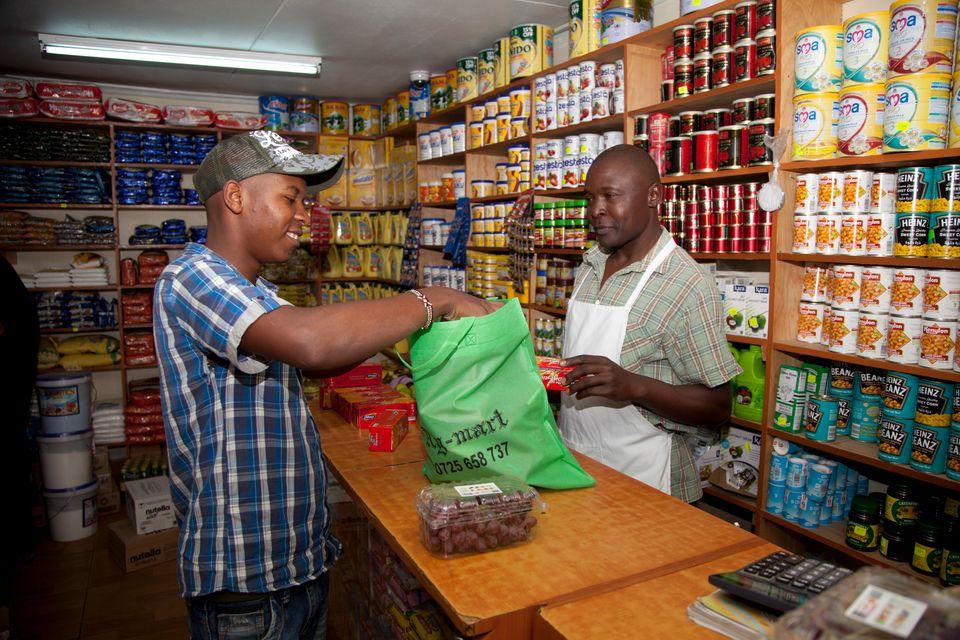 Un client emballe ses provisions dans un sac en tissu à Nairobi, le 28 août 2017, date à...