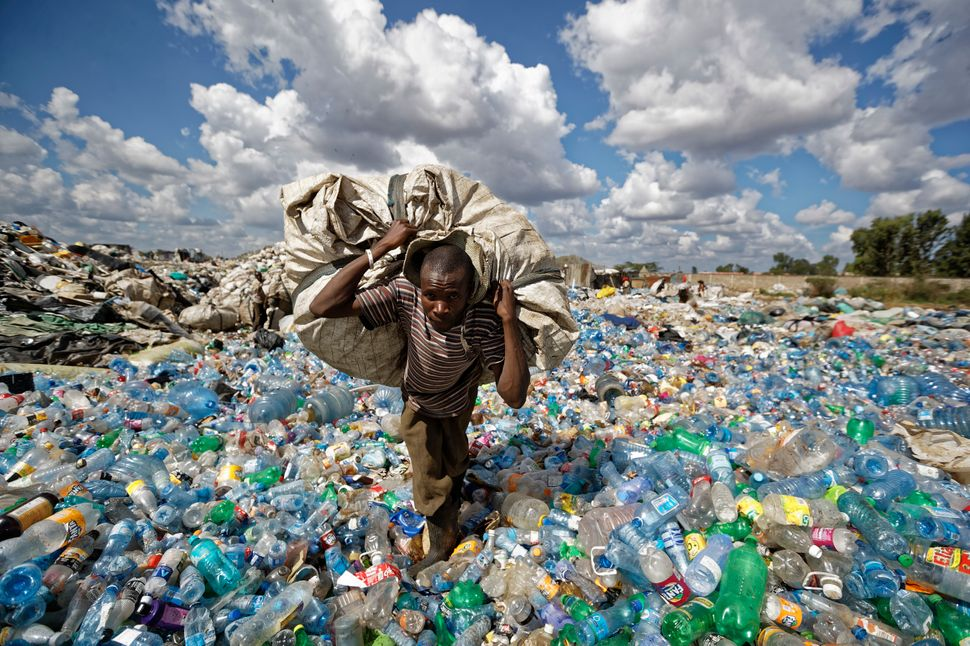 A man walks on a mountain of plastic bottles as he carries a sack of them to be sold for recycling after weighing them at the