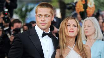 """CANNES, France:  US actor Brad Pitt and his wife Jennifer Aniston arrive for the official projection of US director Wolfgang Petersen's (5R) film """"Troy"""" , 13 May 2004, at the 57th Cannes Film Festival in the French Riviera town. Hollywood took over the French Riviera today as Brad Pitt and his co-stars of the epic movie arrived to present their 175 million dollar (147 million euro)-plus swords-and-sandals feature, being shown out of competition, in the blaze of Cannes publicity.AFP PHOTO/BORIS HORVAT  (Photo credit should read BORIS HORVAT/AFP via Getty Images)"""