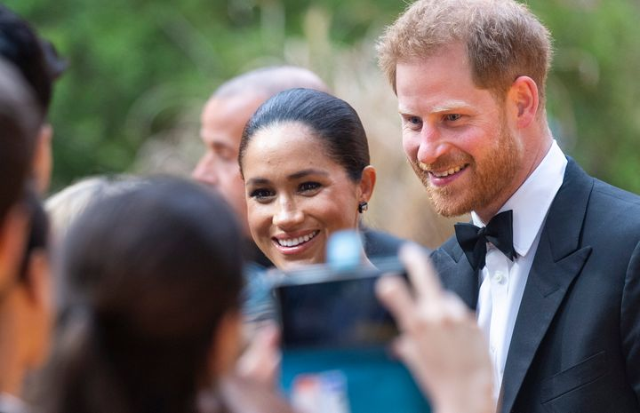 """A fan snaps a photo of Meghan and Harry at the London premiere of """"The Lion King"""" on July 14."""