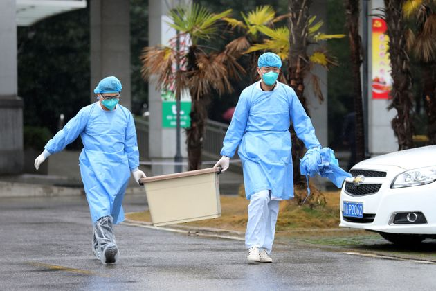 Medical staff carry a box as they walk at the Jinyintan hospital, where the patients with pneumonia caused...