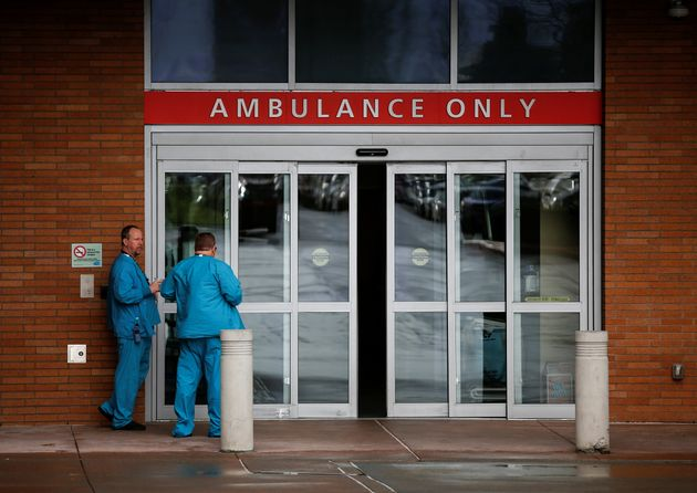 Employees in scrubs talk next to the ambulance entrance at Providence Regional Medical Center after a...