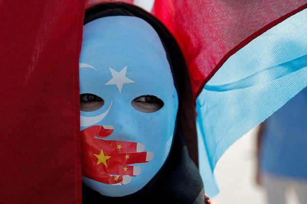 Un uigur con una máscara protesta contra China frente a la embajada de este país en
