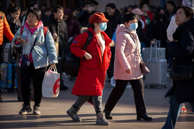 Travelers wear face masks as they walk outside of the Beijing Railway Station in Beijing, Monday, Jan....