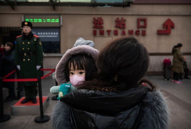 A Chinese girl wears a protective mask as she's held by a relative at a railway station in Beijing on...