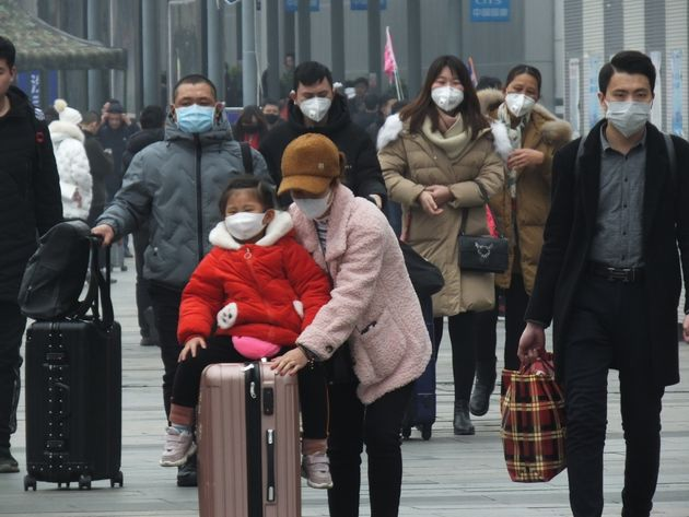 Travellers wearing protective masks walk Tuesday in Yichang, China. Health officials are warning people...