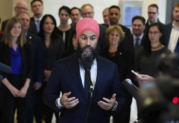 NDP Leader Jagmeet Singh stands in front of his caucus as he speaks to reporters after the weekly caucus...