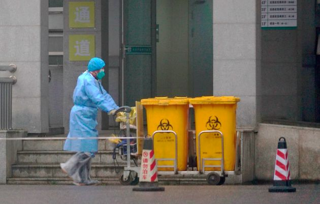 Staff move bio-waste containers past the entrance of the Wuhan Medical Treatment Center, where some infected...
