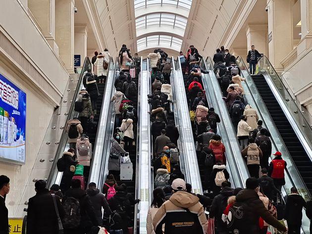 WUHAN, CHINA - JANUARY 22: People wearing face masks ride escalators inside Hankou Railway Station on...