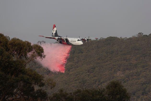A large air tanker (LAT) drops retardant near a property on January 10, 2020 in Penrose,