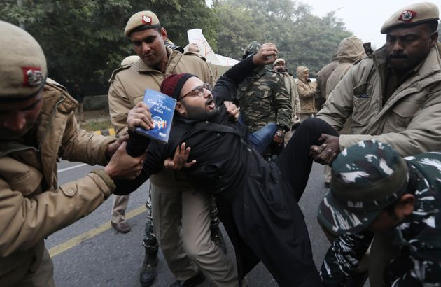 Police officers detain a protesting against the new citizenship law outside Uttar Pradesh Bhawan ...