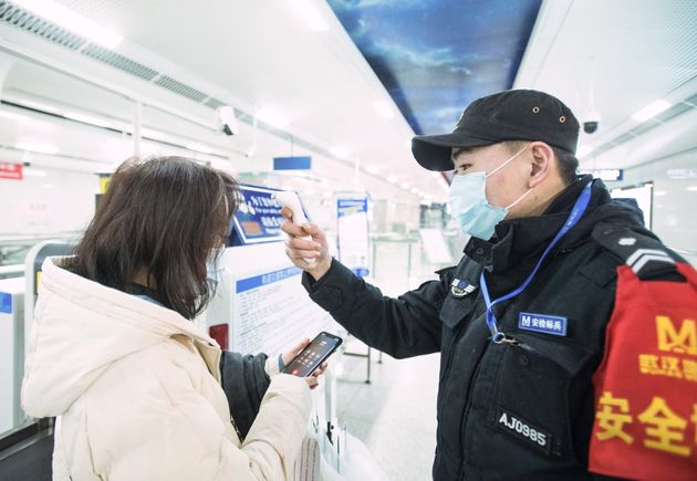 In this photo released by China's Xinhua News Agency, an official checks a passenger's temperature at...