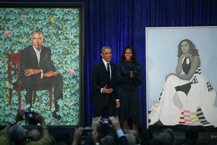 Former U.S. President Barack Obama and former first lady Michelle Obama stand next to their newly unveiled portraits during a
