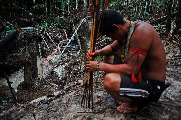 Munduruku warriors arrive at an area of jungle cleared by wildcat gold miners as they search for illegal gold mines and miner