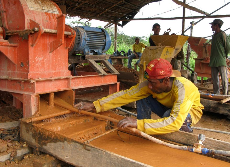 A Brazilian gold miner cleans a rock crusher in Bom Jesus along the Tapaj´s