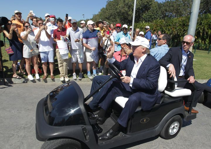 Then-presidential candidate Donald Trump drives himself around the golf course to watch the final round of the Cadillac Champ