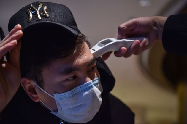 A hotel employee takes the temperature of a person that just arrived at the premise in Wuhan on Jan....