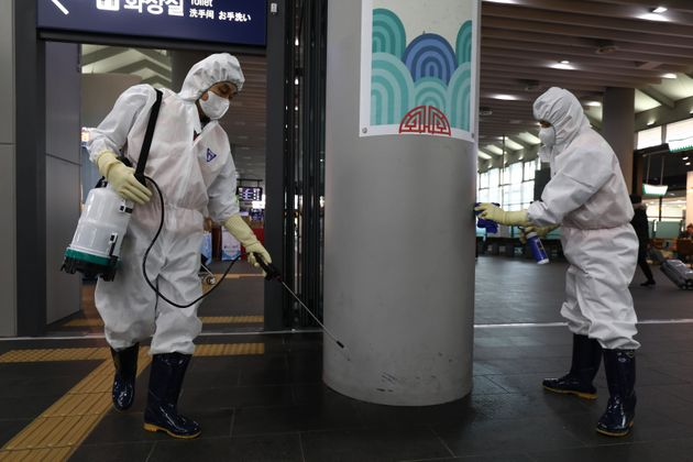 Disinfection workers wearing protective gears spray anti-septic solution in an train terminal amid rising...