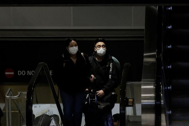 Travellers wearing masks arrive on a direct flight from China, after a spokesman from the U.S. Centers...
