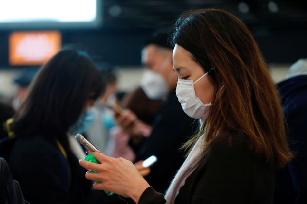Passengers wear masks to prevent an outbreak of a new coronavirus at the Hong Kong West Kowloon High...