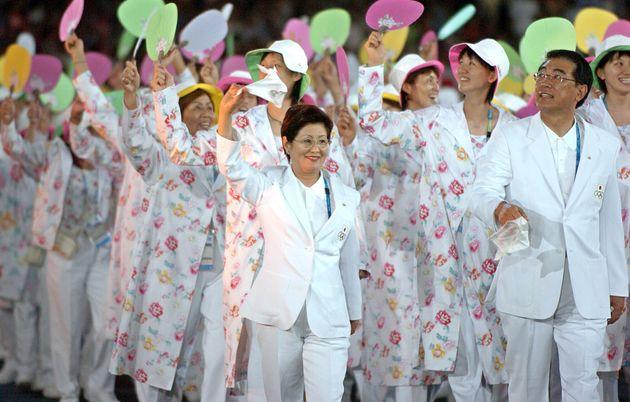 カラフルな団扇を手に、アテネオリンピックの開会式で入場行進する日本選手団(2004年)