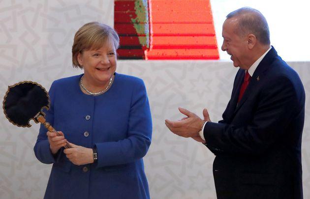 Η Καγκελάριος της Γερμανίας Αγκελα Μέρκελ αντιδρά ξαφνιάζοντας με τον ενθουσιασμό της καθώς δέχεται εθιμοτυπικά δώρα από τον Τούρκο Πρόεδρο Ταγίπ Ερντογάν στην Κωνσταντινούπολη, στις 24 Ιανουαρίου 2020. REUTERS/Umit Bektas