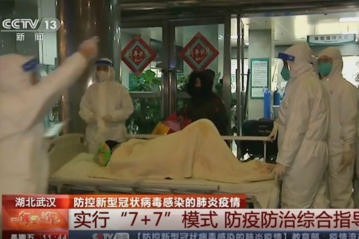 China's CCTV shows a patient being carried on a stretcher to an ambulance by medical workers in protective suits in Wuhan, Ch