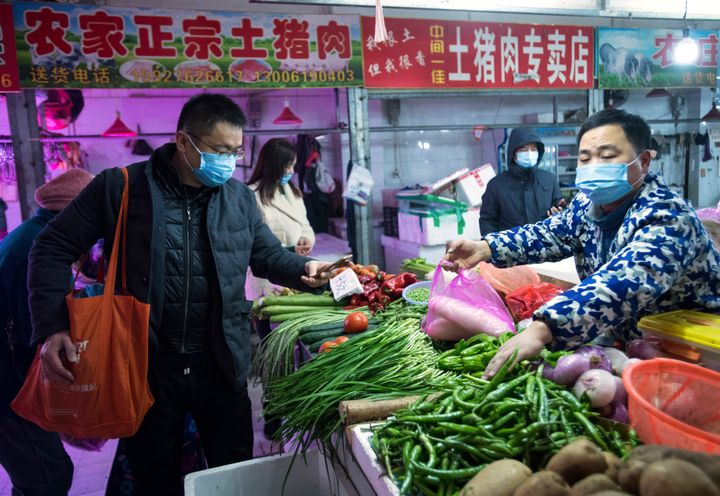 In this photo released by China's Xinhua News Agency, people shop for vegetables at a market in Wuhan in central China's Hube