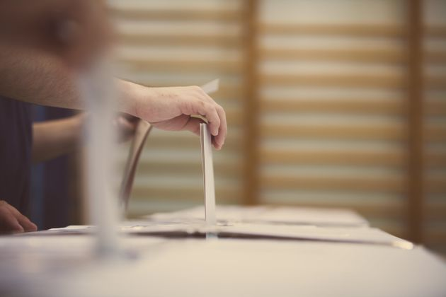Hand of a person casting a ballot at a polling station during