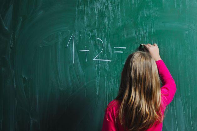 Una niña realiza una suma en la pizarra: no sabemos si