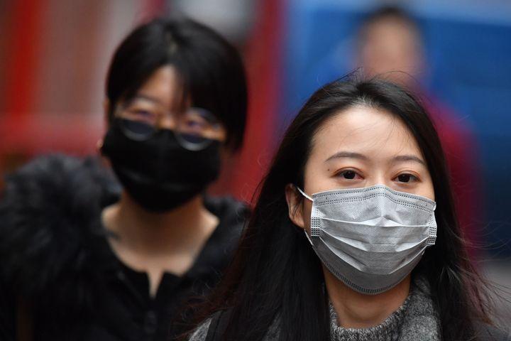 Des piétons portent des masques dans le quartier chinois de Londres, le 24 janvier 2020 (photo d'archives)