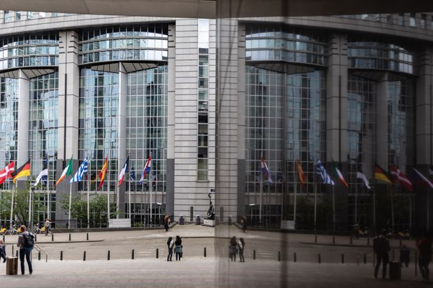 26 May 2019, Belgium, Brüssel: An entrance to the European Parliament is reflected in a glass façade....