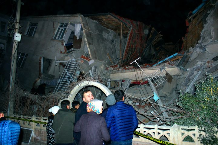 People look at a collapsed building after a 6.8 earthquake struck Elazig city centre in the eastern Turkey on Friday.