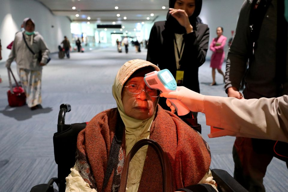 A health official scans the body temperature of a passenger as she arrives at the Soekarno-Hatta International...