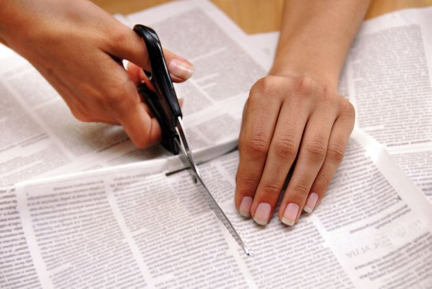 hand with scissors cutting out an article from